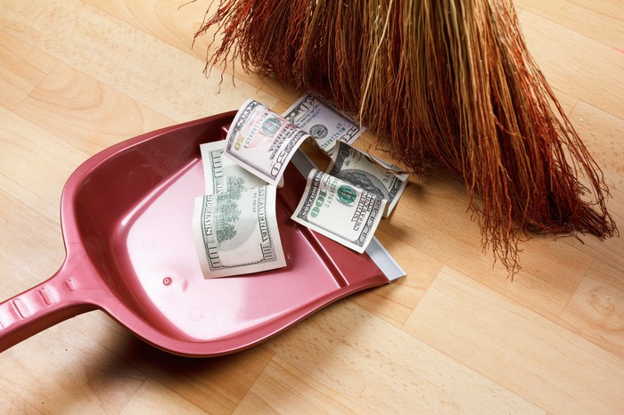 A broom sweeps paper currency into a red dustpan.