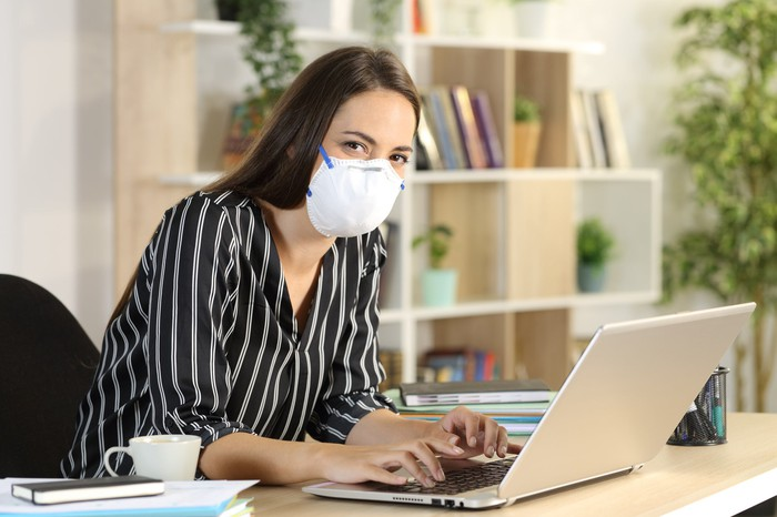 A young woman wearing a face mask works with a laptop at her living room table.