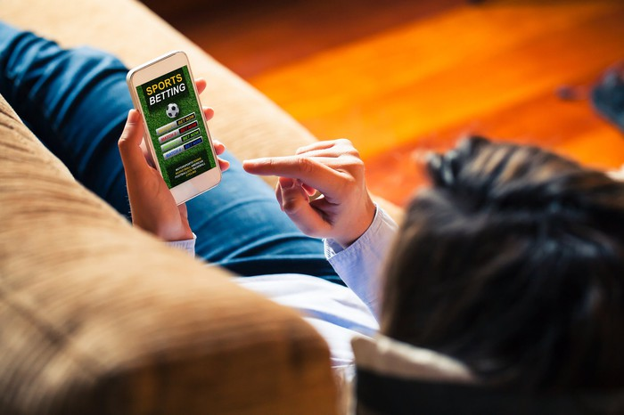 online sports gambler on couch with smartphone making bets