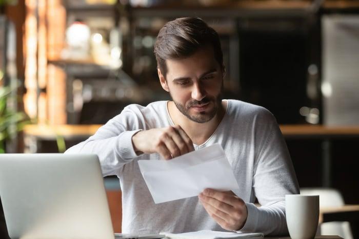 Man at laptop opening envelope
