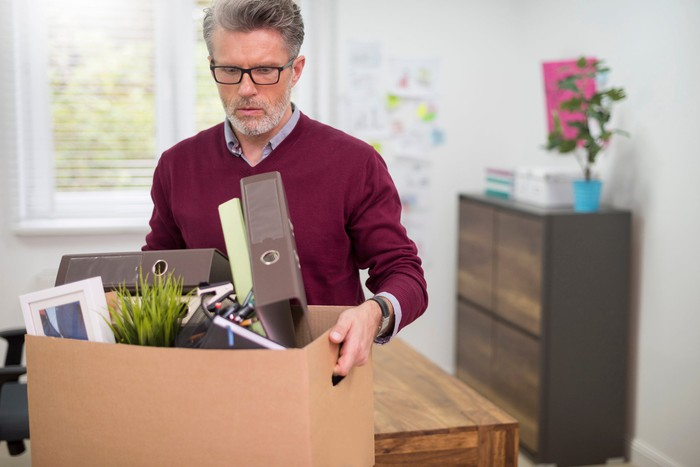 Older man holding large cardboard box of office supplies