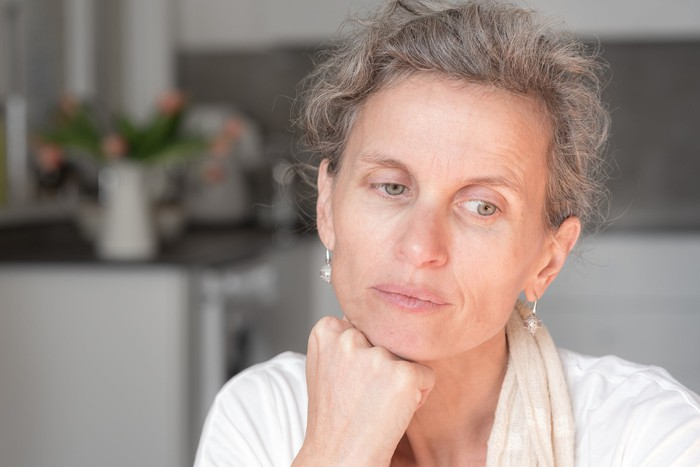 Older woman with serious expression resting head on fist