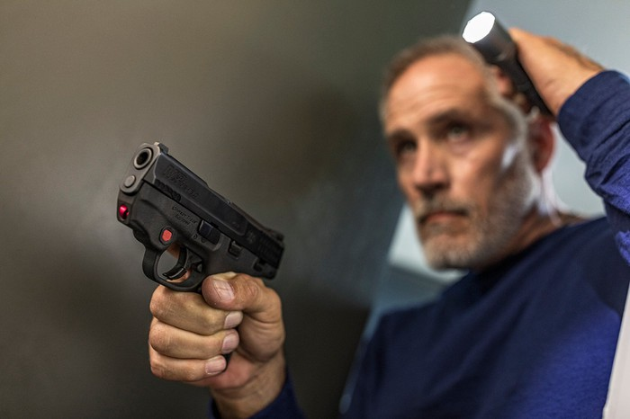 Man with laser-sighted pistol and flashlight