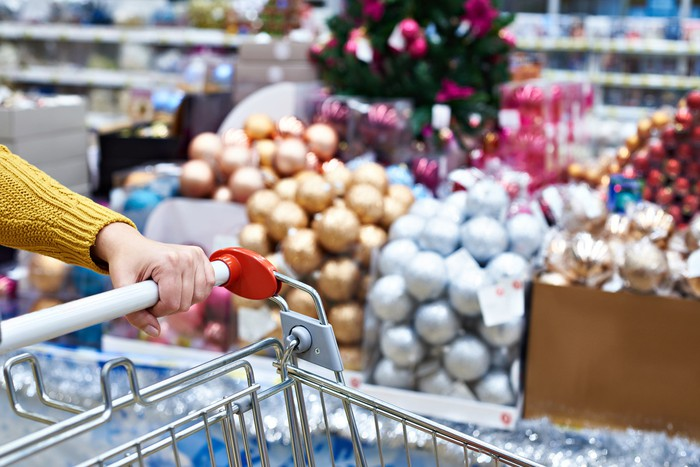 A woman holding pushing a shopping cart in front of some Christmas ornament balls