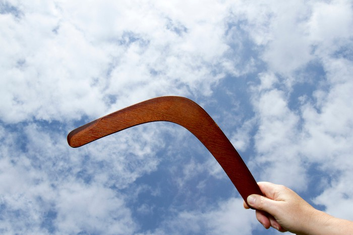 A hand is throwing a wooden boomerang into a cloudy sky.
