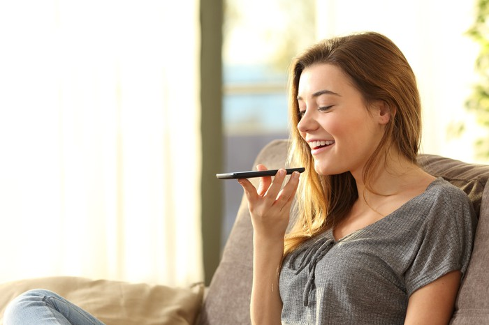 A young woman using a smartphone's voice recognition feature.