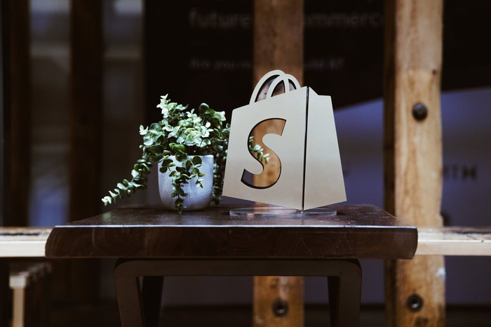 The Shopify logo on a virtual bag sitting on a table.