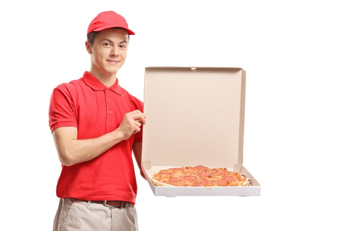 Pizza delivery boy with a red shirt and red cap holding an open pizza delivery box.