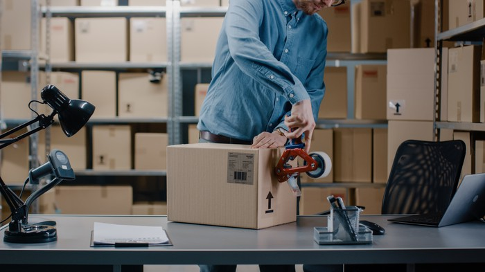 A man in a warehouse packing a box to ship.
