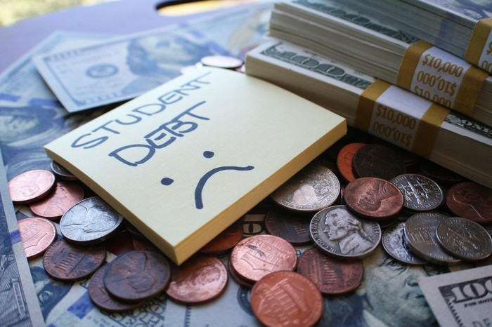 A sticky note pad with the words student debt on it over a sad face. The pad sits atop a pile of change and stack of bills.