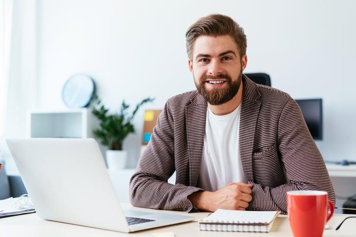 Smiling young man at laptop