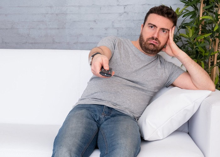 Man with pained expression on couch holding TV remote