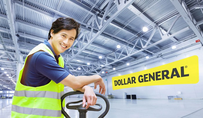 Person next to forklift with Dollar General logo on the wall in a warehouse.