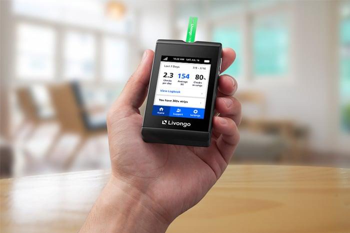 A man's hand holding a Livongo diabetes meter.