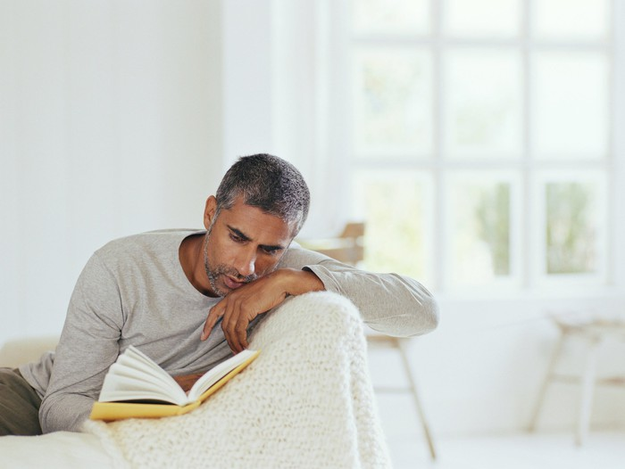 Middle-aged man reading book