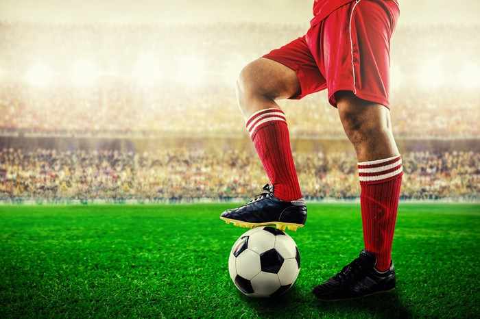 Bottom half of a pro soccer player holding a ball with his foot.