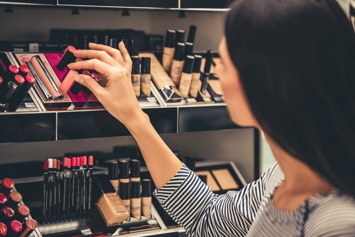 Women touching various cosmetics on a shelf in a store.