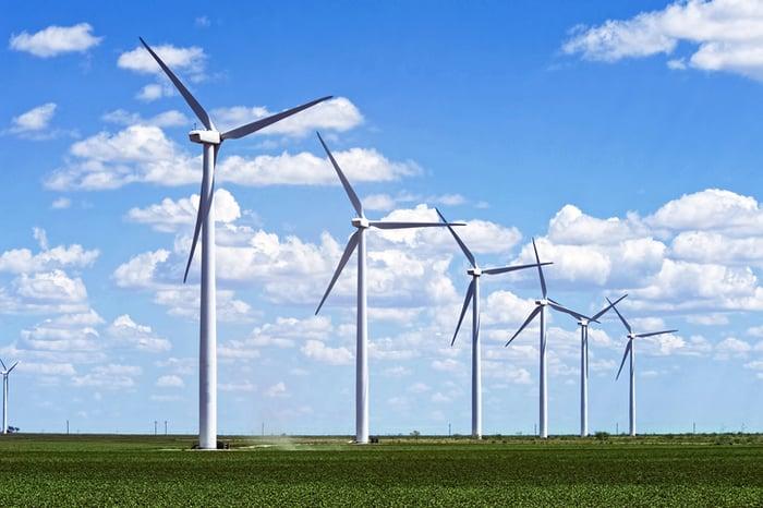A row of wind turbines in a field.