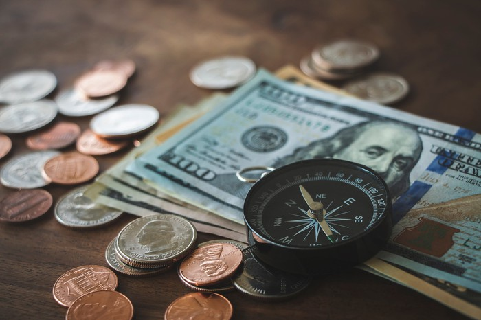 A compass on top of cash and coins.