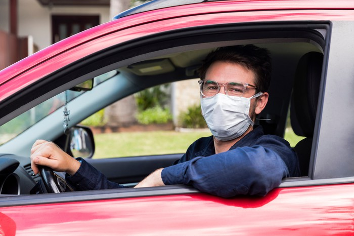A Uber driver wearing a mask in a red vehicle.
