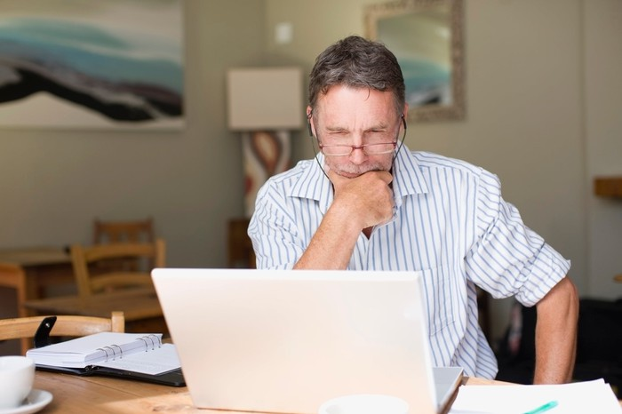 A man sitting in front of a laptop, looking pensive