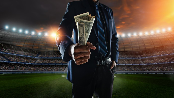 a man in a suit holds up a wad of money while standing in front of a shadowed image of a sports stadium full of people