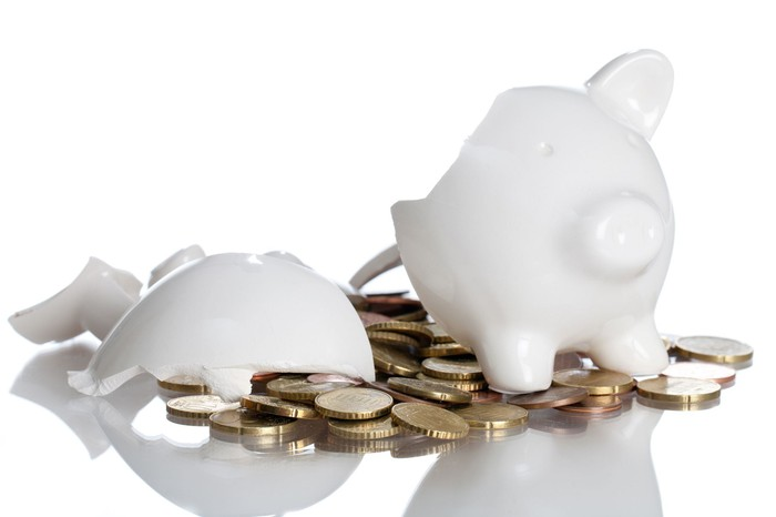 A broken white piggy bank with coins spilling out.