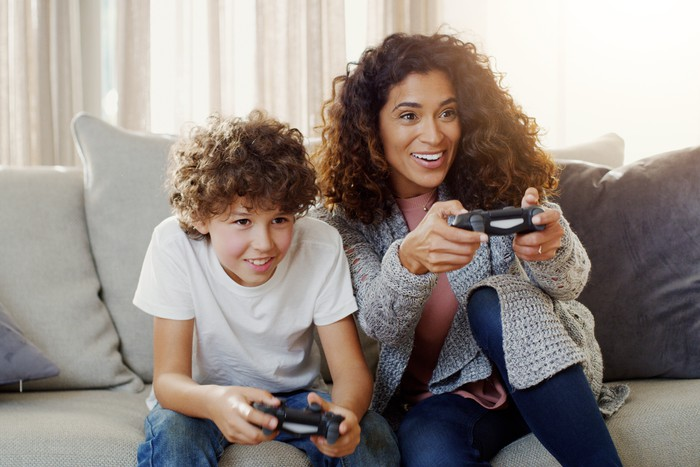 A mom and son playing video games in their living room.