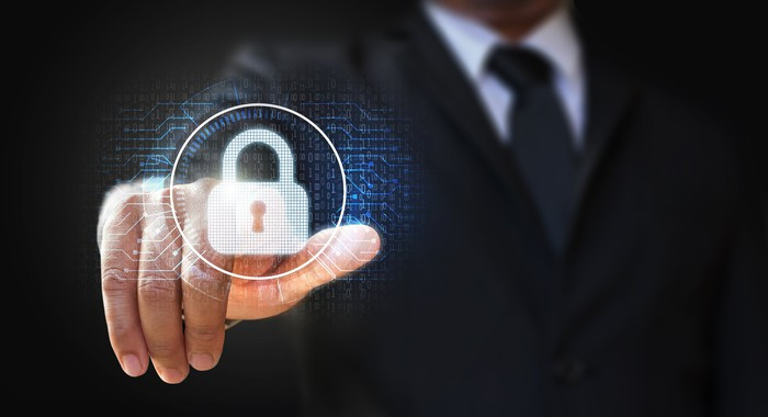 A person in a business suit is pointing to a digital image of a lock.