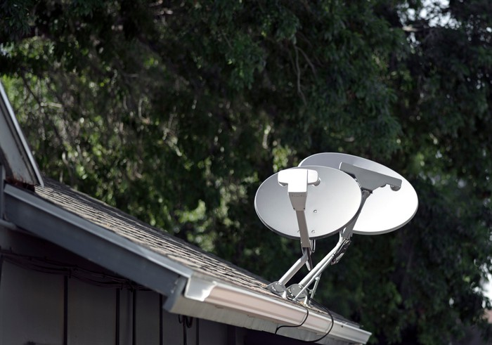 A pair of satellite dishes on a roof.