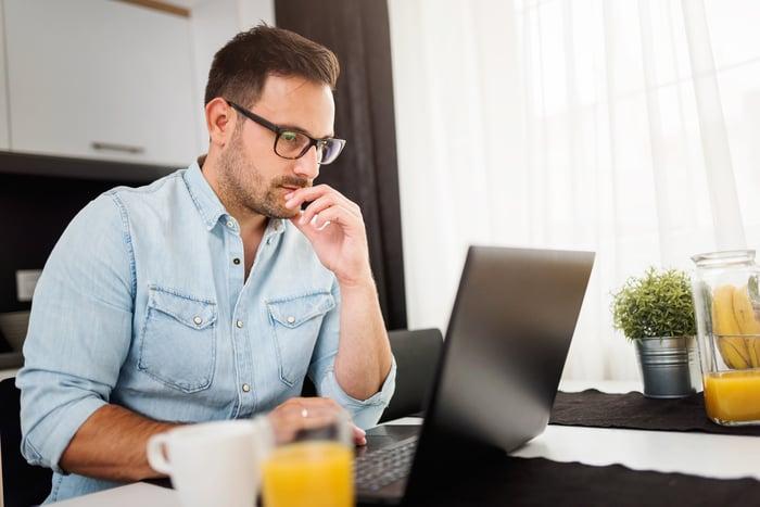 Man using laptop computer, working at home.