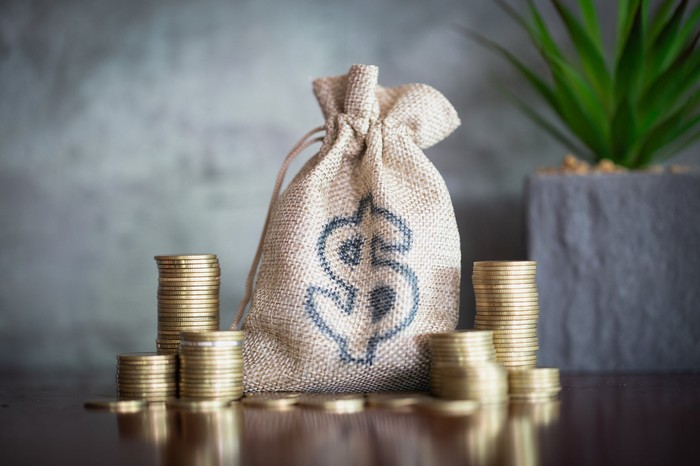 Burlap drawstring bag printed with a dollar sign and stacks of coins sitting on a table.