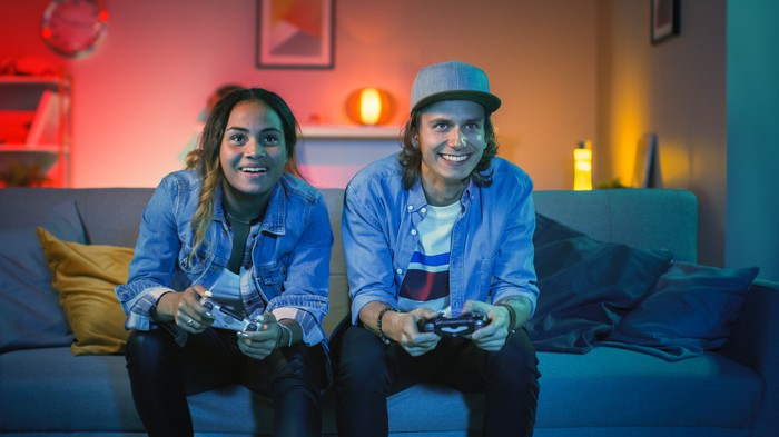 A young man and woman playing console video games while seated on a couch.