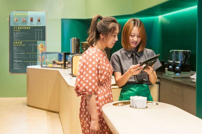 A Starbucks barista assists a woman ordering at a Starbucks Now location in China.