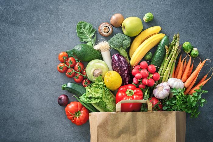 A full brown bag displays an assortment of fresh produce.
