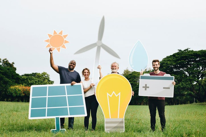 A group of people holding up cutouts of various renewable energy symbols.