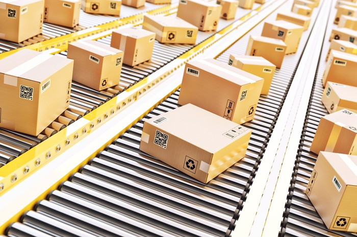 Delivery boxes moving on conveyor belts positioned beside each other.