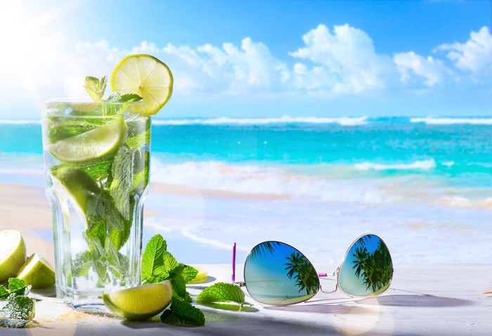 Sunglasses and a glass in front of ocean.