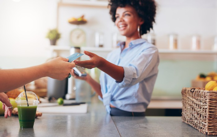 A woman accepting a card for payment in a cafe.