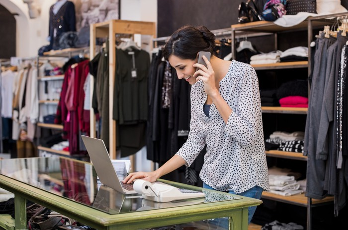 Woman at counter of clothing store typing on laptop and talking on phone