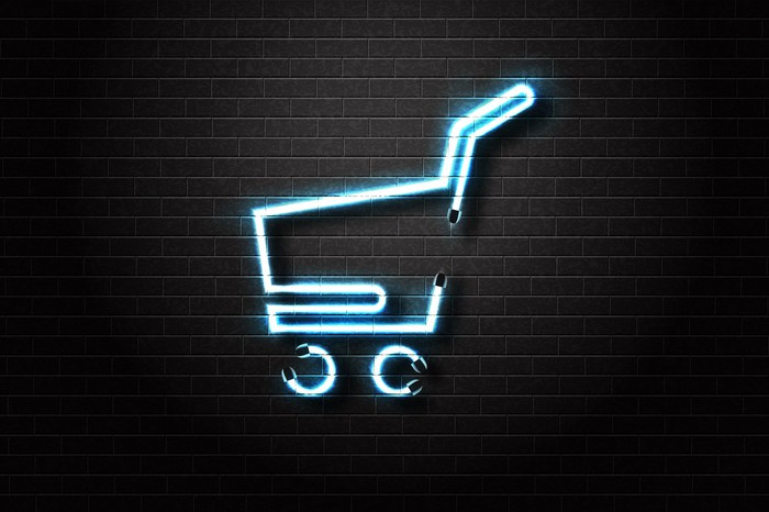 A lit neon sign in the shape of a shopping cart.
