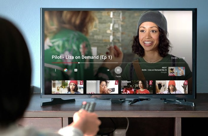 A person pointing a remote at a TV displaying YouTube videos.