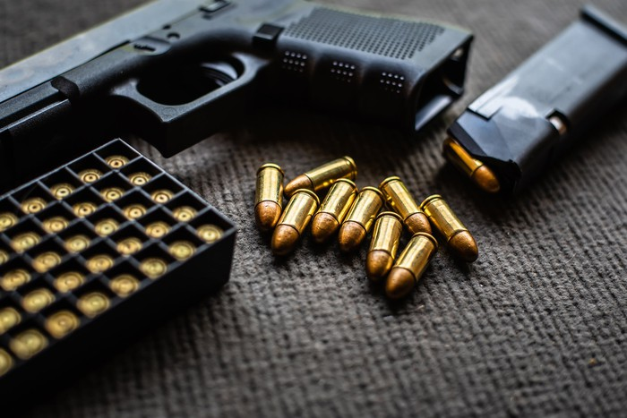 Handgun lying next to a box of bullets and a few loose rounds
