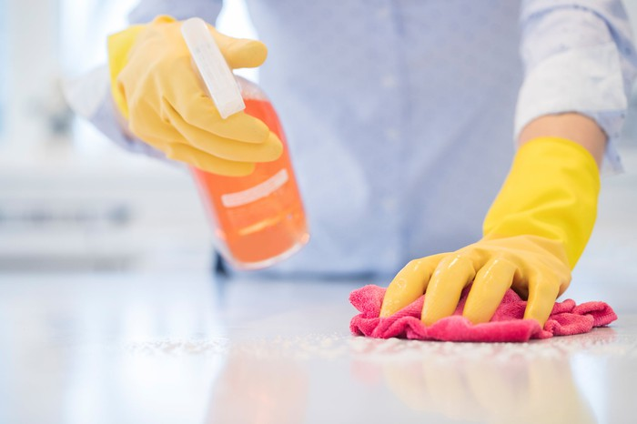 A person disinfects their counter with cleaning spray.