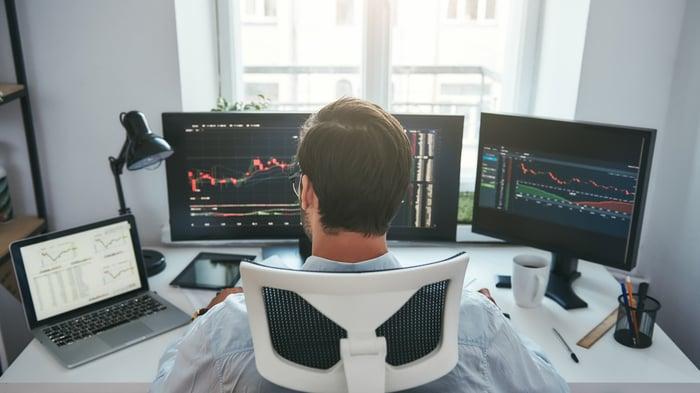 Man looking at several monitors with financial charts.