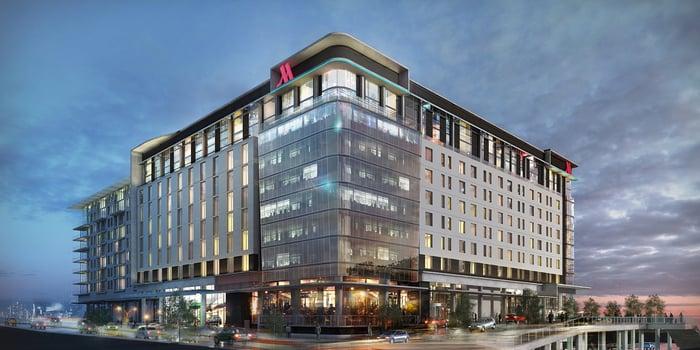 Multi-story hotel building with Marriott logo on side, against an overcast sky near dusk.