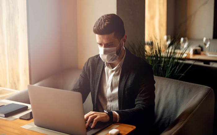 A young man sits at his laptop wearing a face mask.