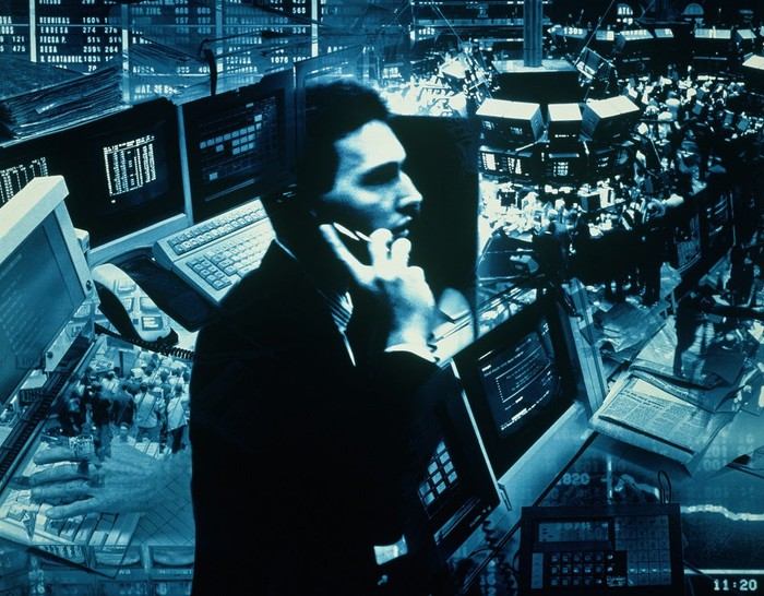 Stockbroker on the phone with trading floor in the background.