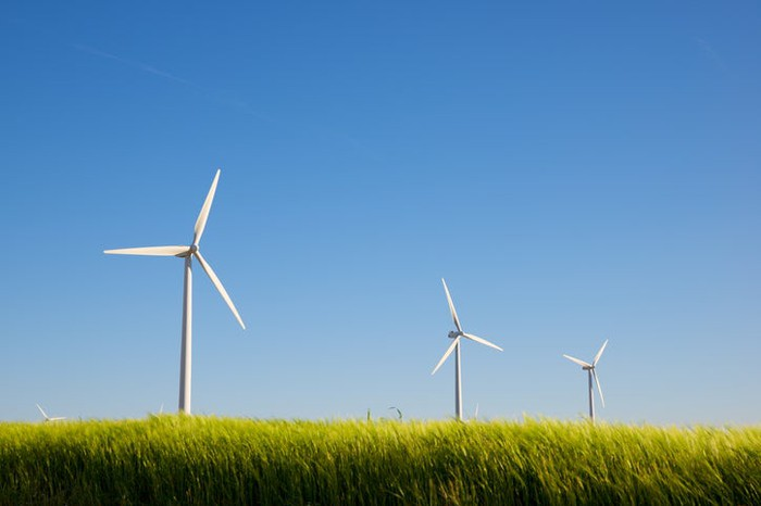 A row of wind turbines in a grassy field.