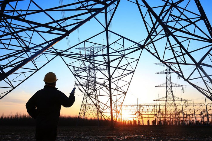 A worker standing under transmission lines.
